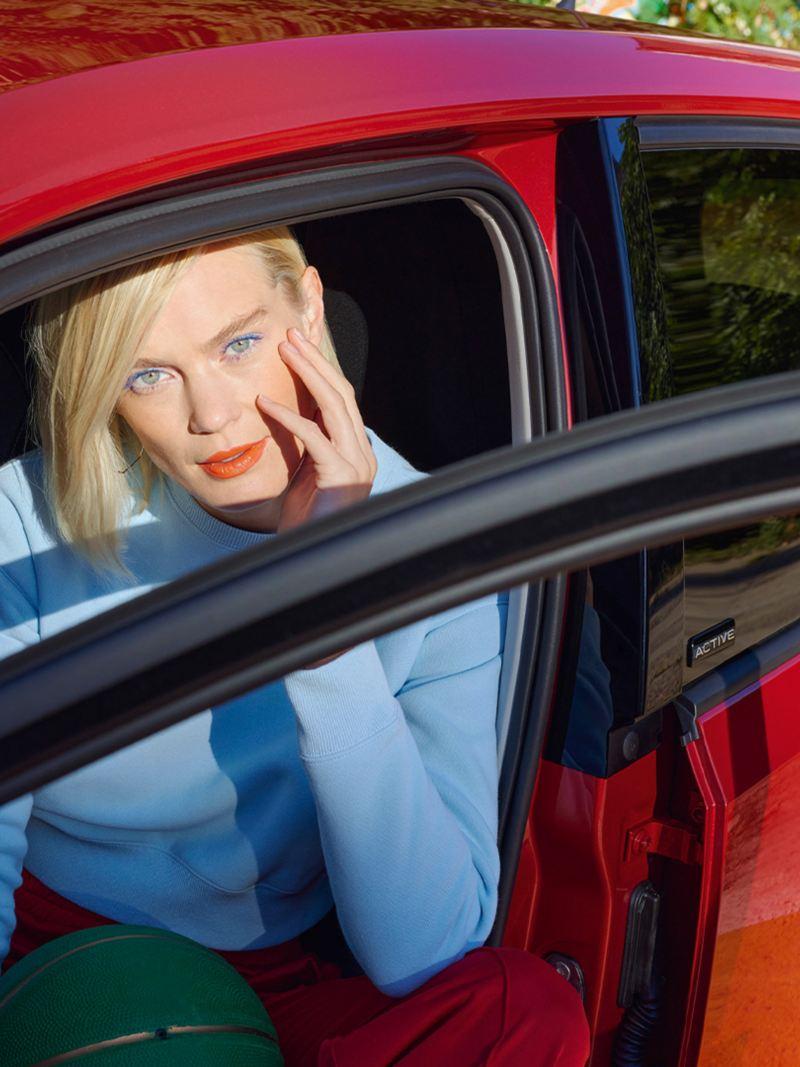 Gros plan du profil d'une VW up! ACTIVE rouge avec une portière ouverte. Une femme vêtue d'un pull bleu du côté conducteur.