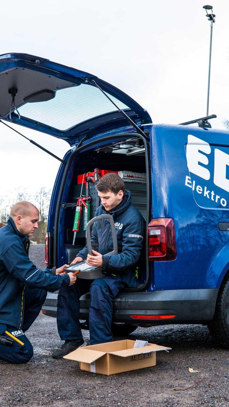 Bildet viser to ansatte fra EDA Elektro og en blå Volkswagen Caddy varebil med Würth bilinnredning