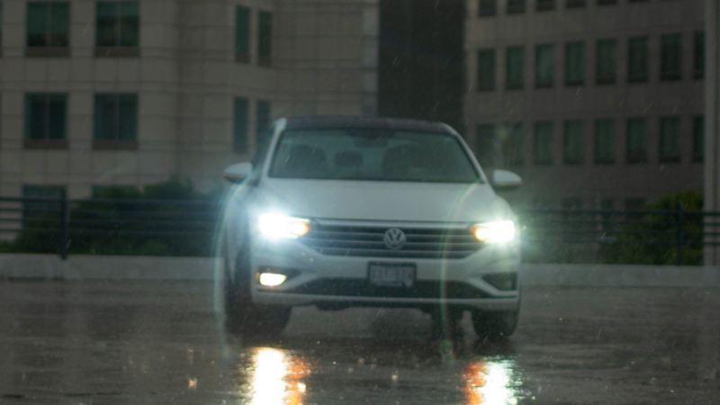 jetta blanco conducido bajo la lluvia