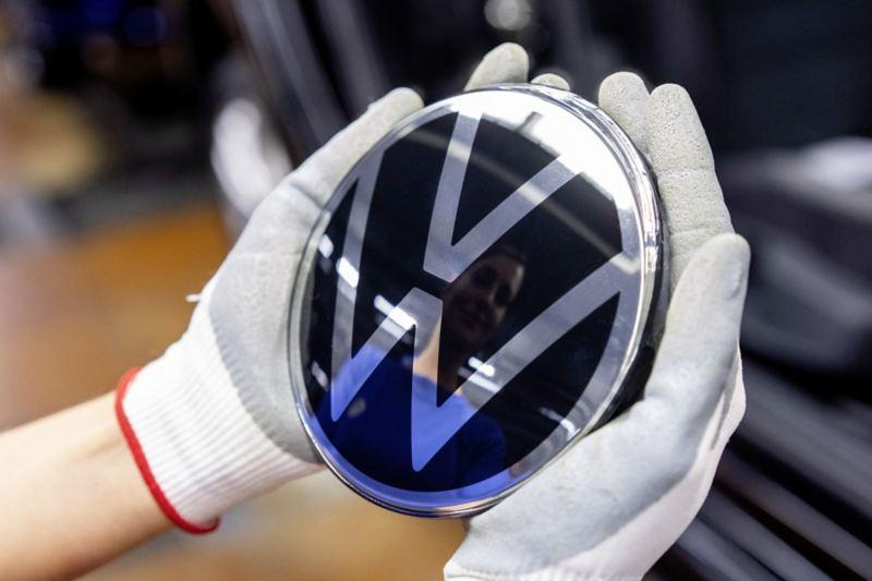 VW Logo liegt in den Händen eines Mitarbeiters