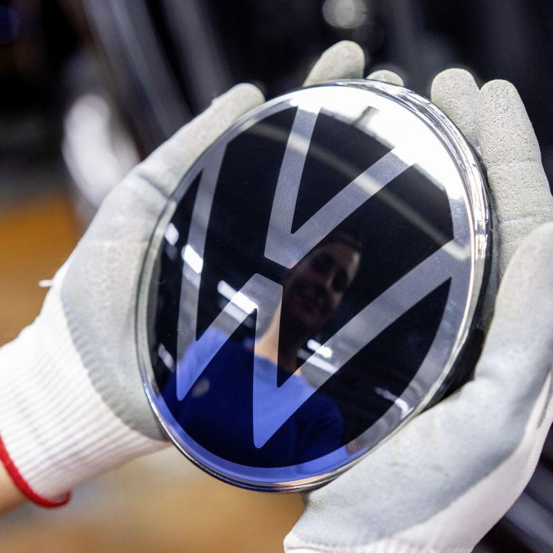 VW Emblem in Händen eines Mitarbeiters