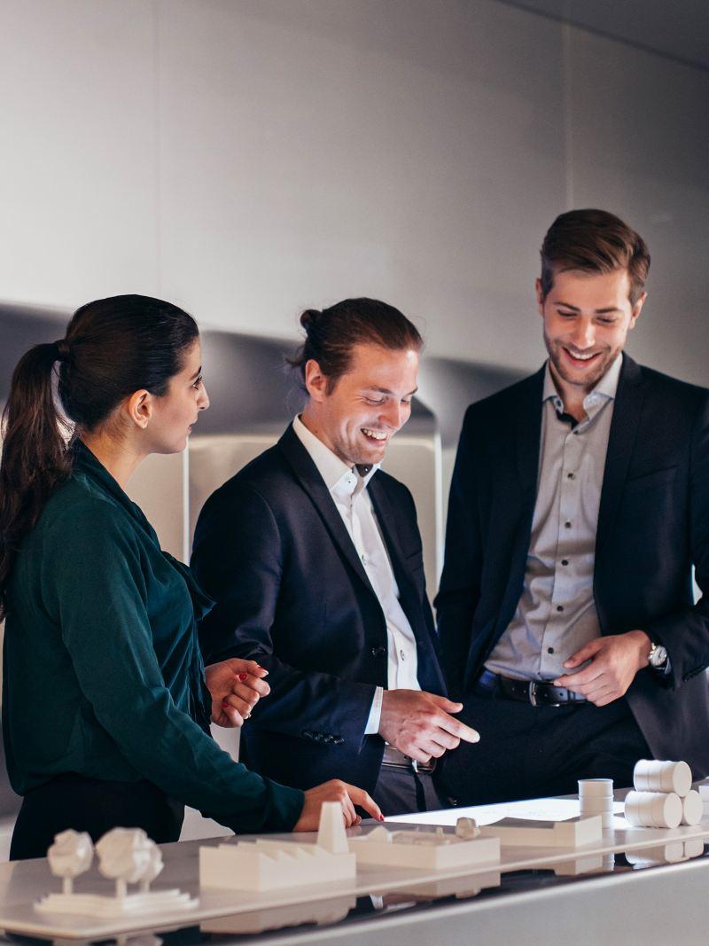 Drei Kollegen betrachten ein Modell und unterhalten sich