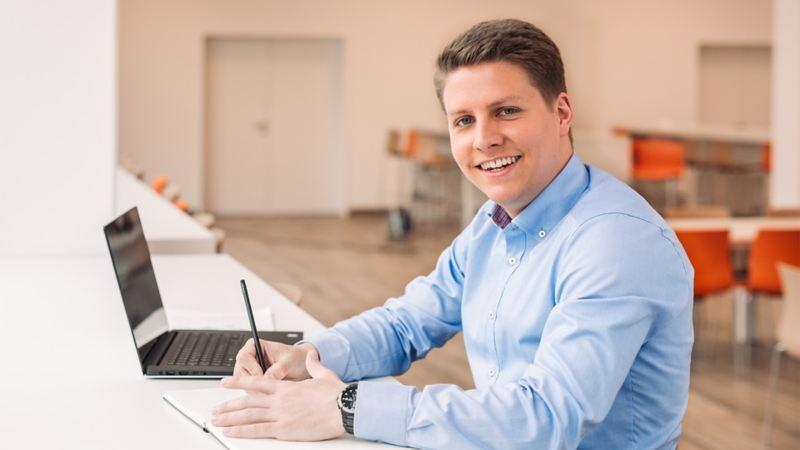 Porträt eines Mannes neben einem Laptop