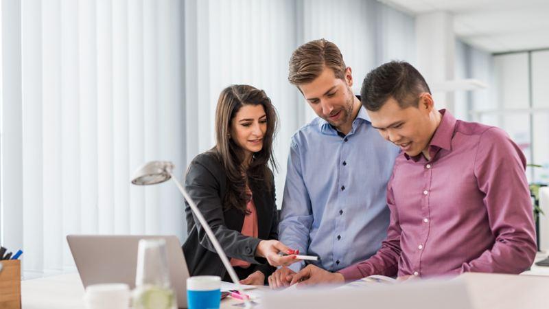 Drei Doktoranden schauen gemeinsam auf ein Projekt