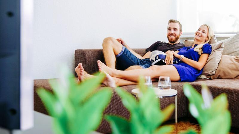 Zwei Personen sitzen auf einer Couch