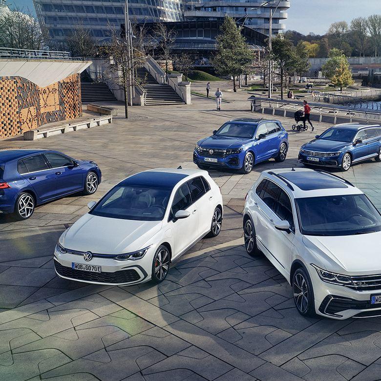 Cinque modelli Volkswagen fermi in un parcheggio. Sullo sfondo uno spazio cittadino.