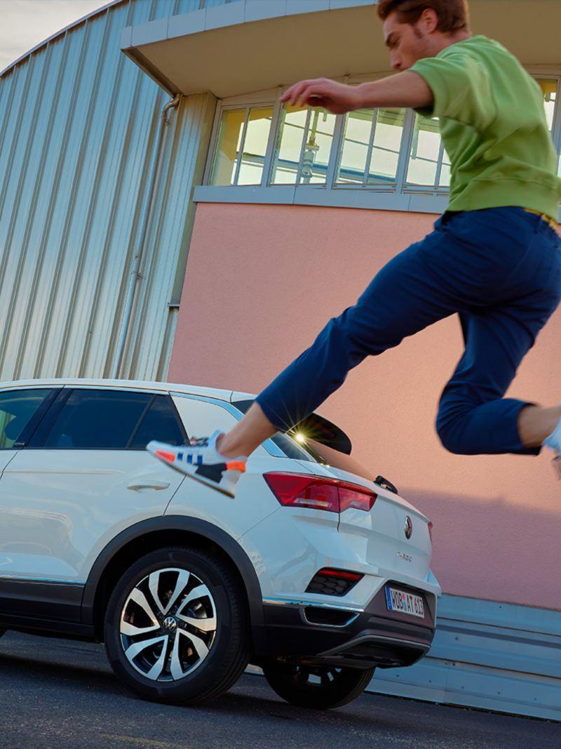 Une VW T-Roc ACTIVE blanche stationnée dans un environnement urbain. Un homme saute dans les airs.