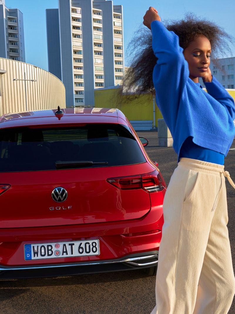 Vue arrière de la VW Golf ACTIVE rouge. Une femme se tient devant elle.