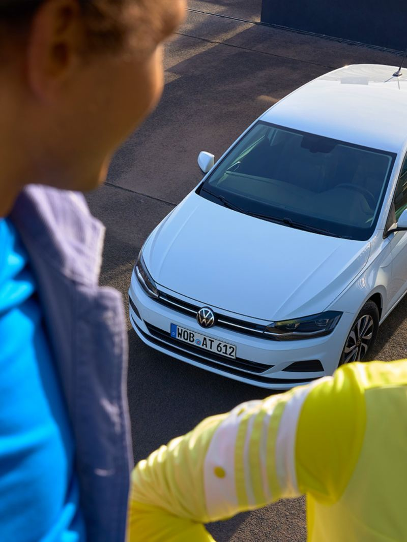 Vue du dessus de la VW Polo ACTIVE blanche. Un homme et une femme sont visibles au premier plan.