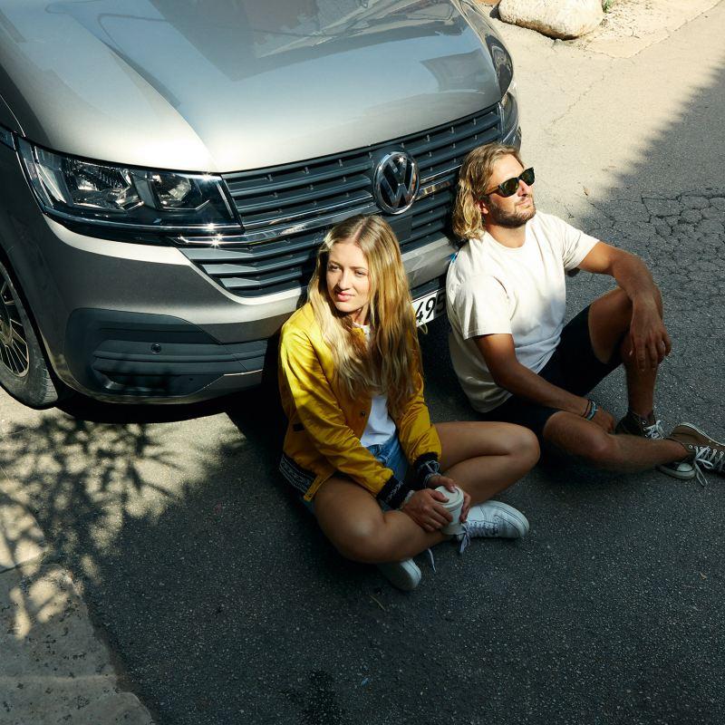 Un couple qui se détend devant un bus VW.