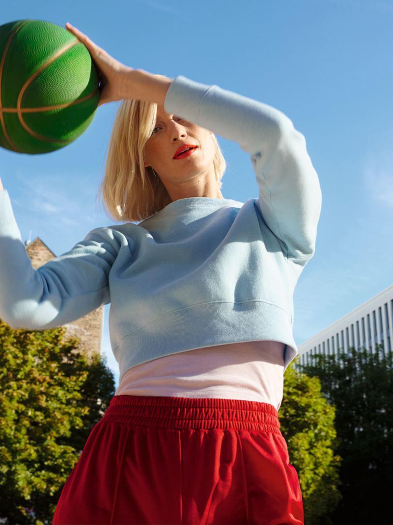 Une femme saute avec un ballon de basket dans les mains. Un décor urbain avec une ville et un espace vert en arrière-plan. Lifestyle.