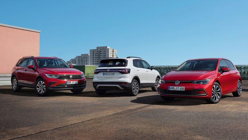 Modèles spéciaux VW ACTIVE. Gamme présentant une Golf ACTIVE rouge, un T-Cross ACTIVE blanc et un Tiguan ACTIVE rouge. Décor urbain.