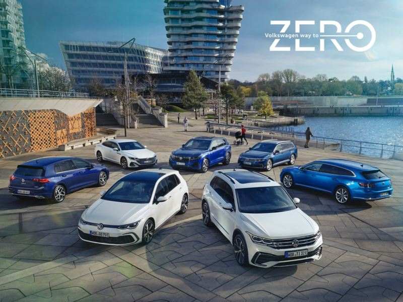 Top view of four blue and three white VW hybrid models on a sunny waterfront.