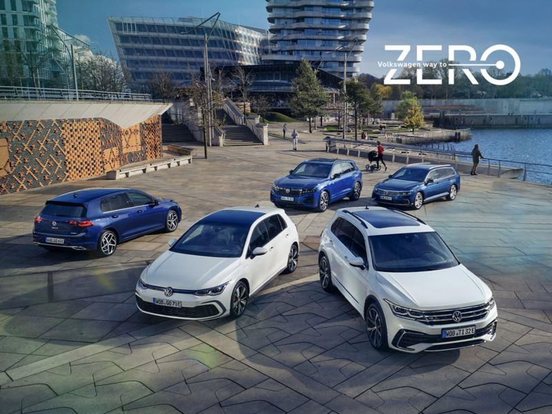 Vista dall'alto su cinque modelli ibridi VW, tre blu e due bianchi, parcheggiati su una grande terrazza panoramica soleggiata accanto a un bacino d'acqua.