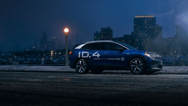 A blue VW ID.4 electric SUV is parked on a snowy road with a nighttime cityscape background