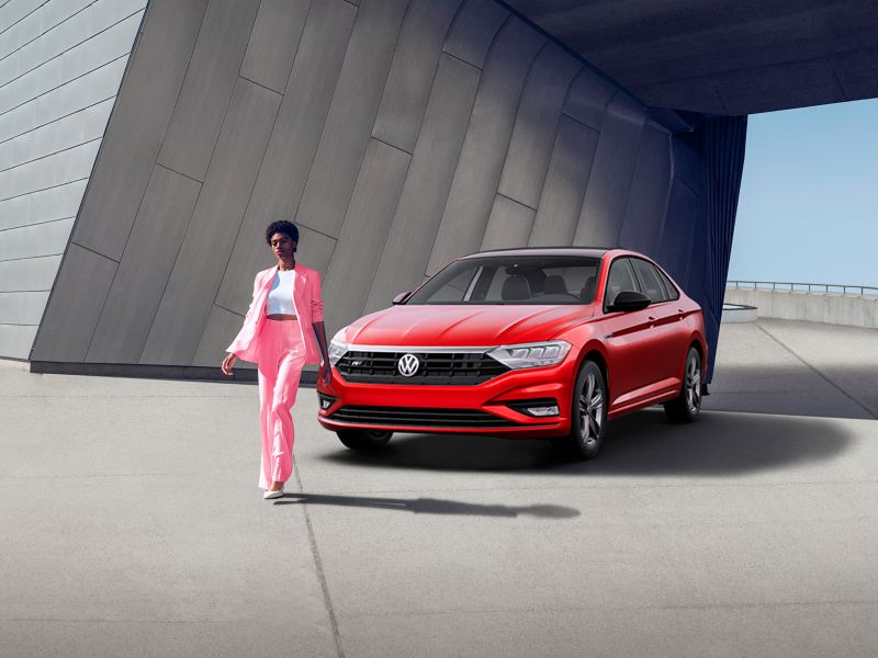 We see a trendy woman in a bright pink pant suit walking away from a red Volkwagen Jetta
