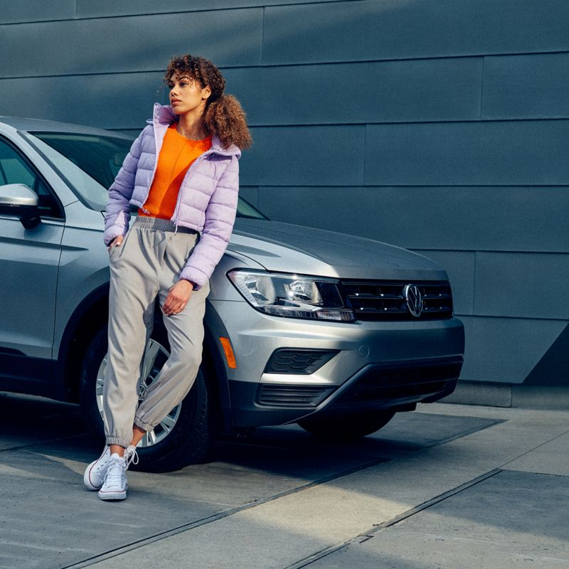 We see a young woman leaning on a silver Volkswagen Tiguan in an urban environment