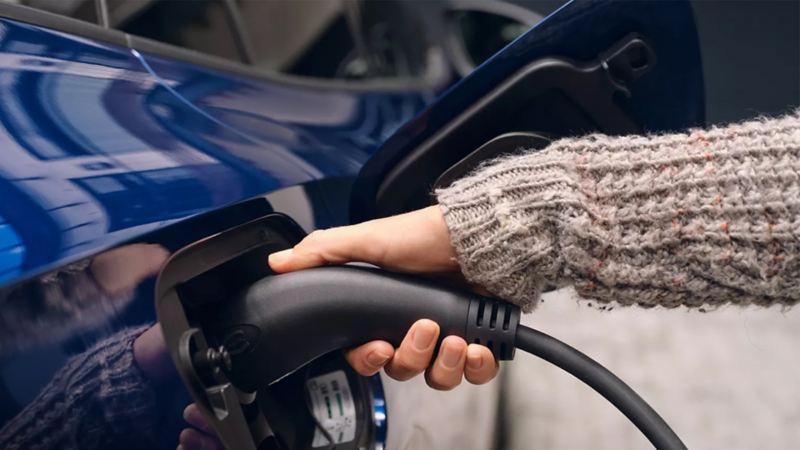 Une personne rechargeant une voiture