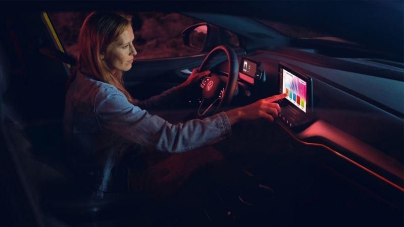 Une femme assise dans un véhicule Volkswagen cliquant sur l'écran tactile