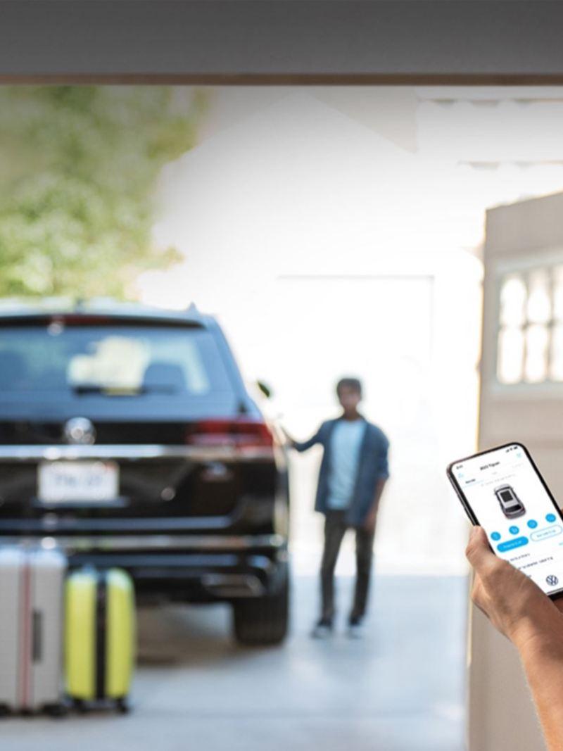 A Car-Net® app on a phone with a VW car in the background