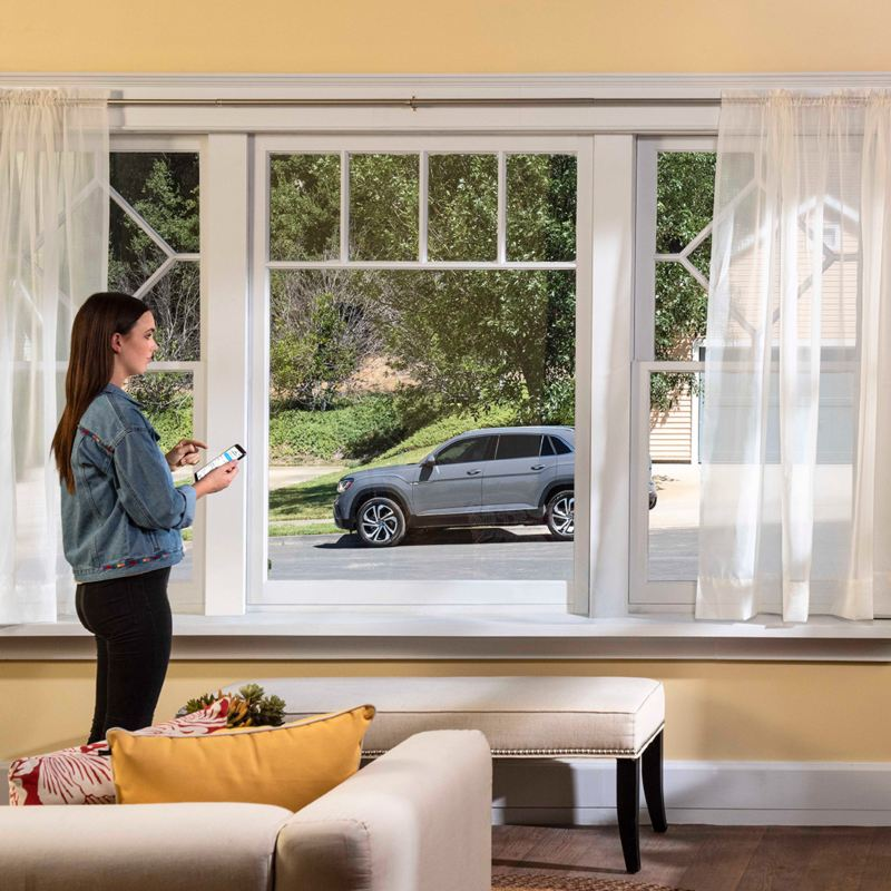 Woman standing in front of window using the remote start feature on the Car-Net® app