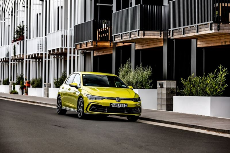 A laughing woman goes to the VW Golf