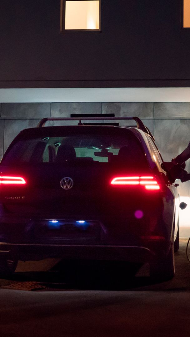 A woman charging up her Volkswagen E golf