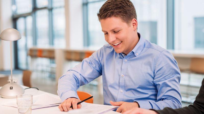 Ein Mann arbeitet mit Stift und Papier an einem Schreibtisch