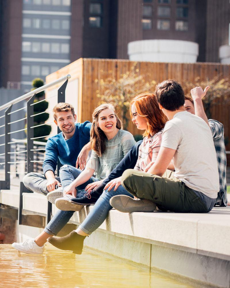 Fünf junge Menschen sitzen gemeinsam am Ufer eines Gewässers
