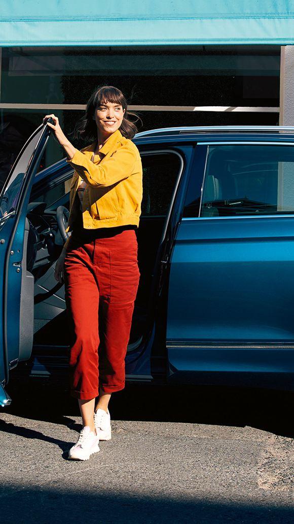 En kvinna stiger ur en VW Tiguan på förarsidan.