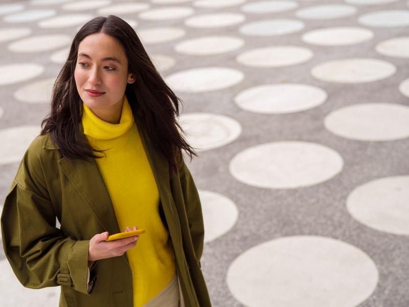 Femme avec son téléphone qui regarde au loin, lien vers la page « Demande de crédit » de VW