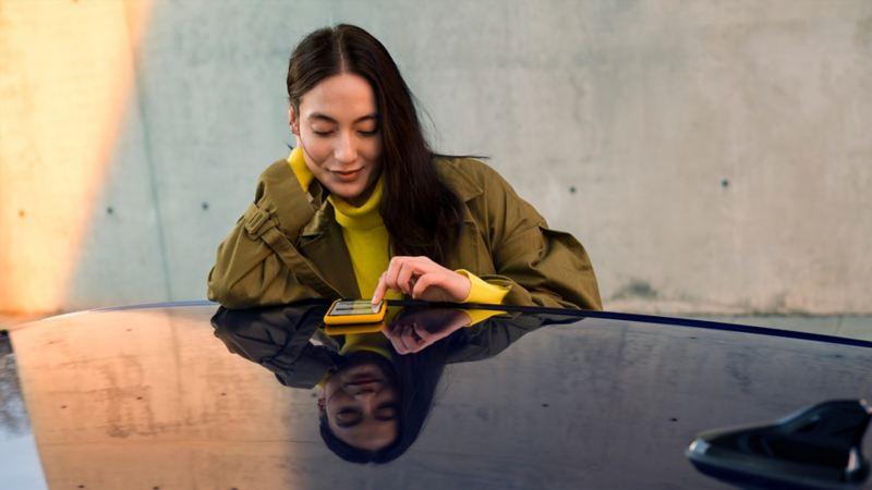 Une femme utilise son téléphone portable sur le toit d'un véhicule Volkswagen
