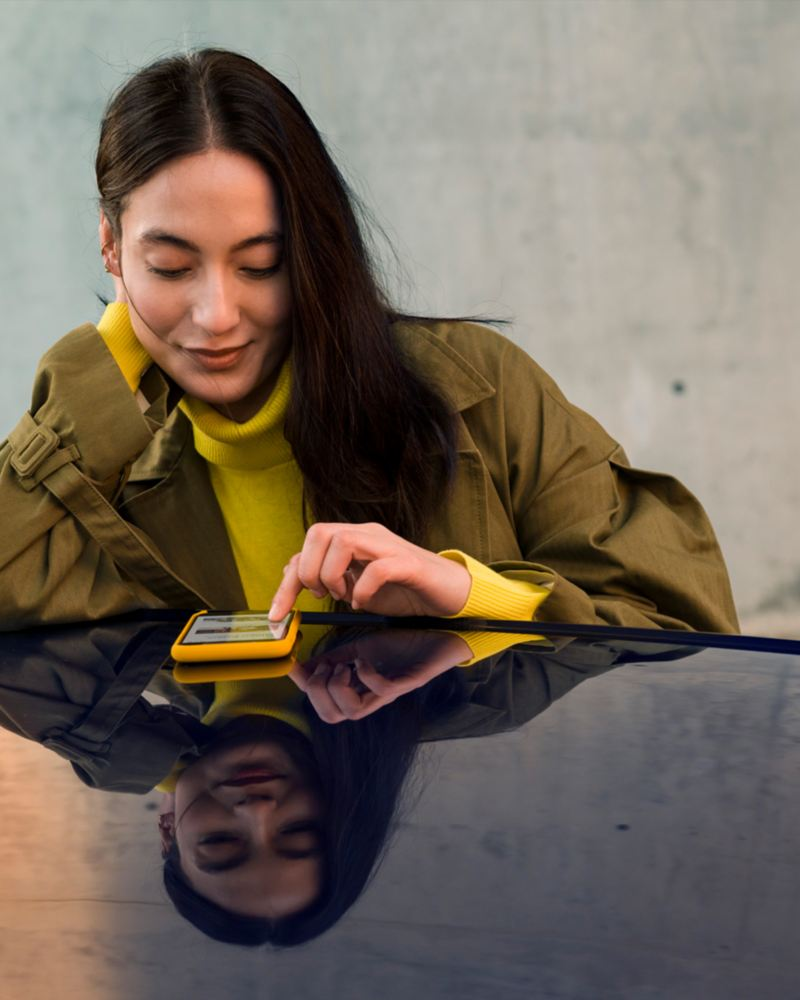 A woman tapping her phone on a Volkswagen roof, link out to offers.vwmodels.ca
