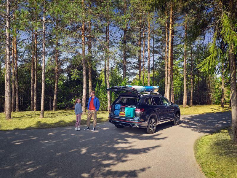 Un père et sa fille se tiennent debouts à côté d'un Atlas aux portes ouvertes et rempli d'équipement de camping, lien vers offers.vwmodels.ca