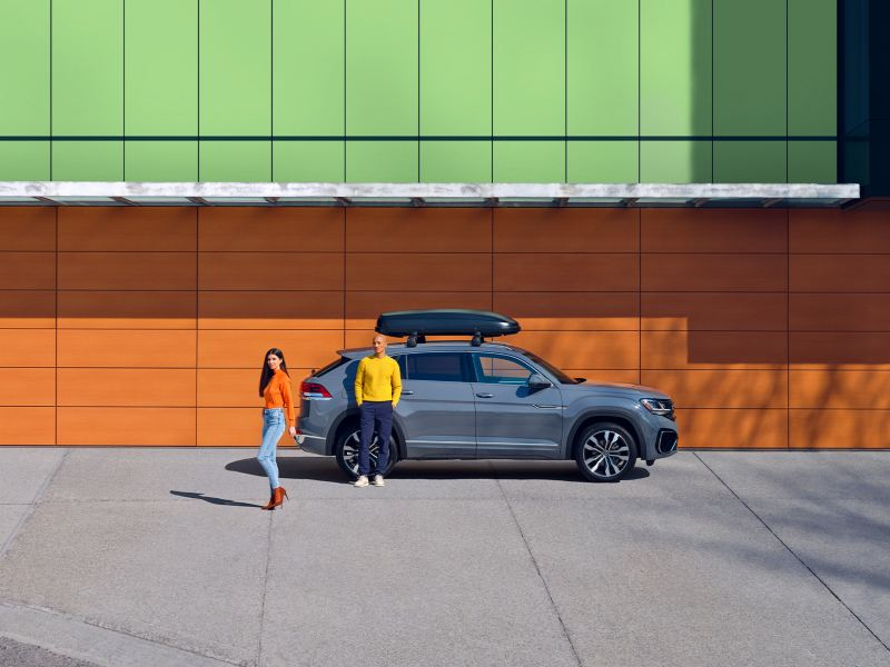 A man and a woman standing infront of a grey Atlas Cross sport in a colour urban environment, outgoing link to offers.vwmodels.ca