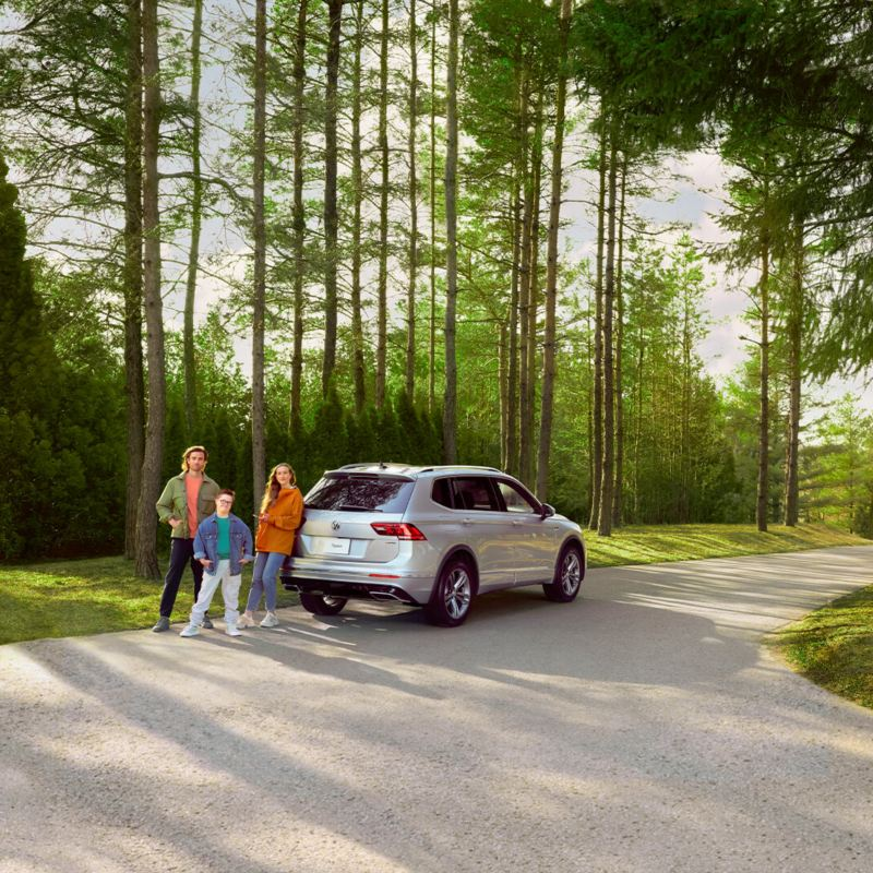 We see a family standing next to a Volkswagen Tiguan in a rural environment with trees.