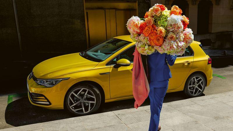 Eine Frau mit Blumenstrauss steht vor dem Golf