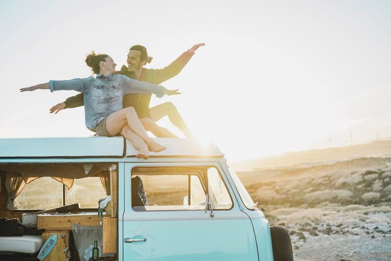 VanLife情境圖 - 情侶坐在Tiffany綠的T2車頂,車側滑門開啟可窺見自行加裝的木製流理台及收納空間
