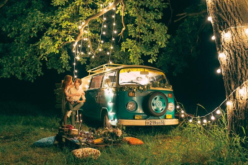 VanLife情境圖 - 老T2停在樹林裡,吊掛燈飾點綴氛圍,情侶坐在車外的高腳椅上,前方草地上矮桌放滿甜點食物酒杯,桌上還有花束點綴,草地上也放了三個不同花紋的坐墊