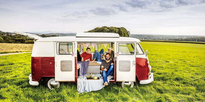 VanLife情境圖 - 3個好友 (2女1男) 開心地或坐或躺在紅白雙色T1車內,背景是山頂的大草原
