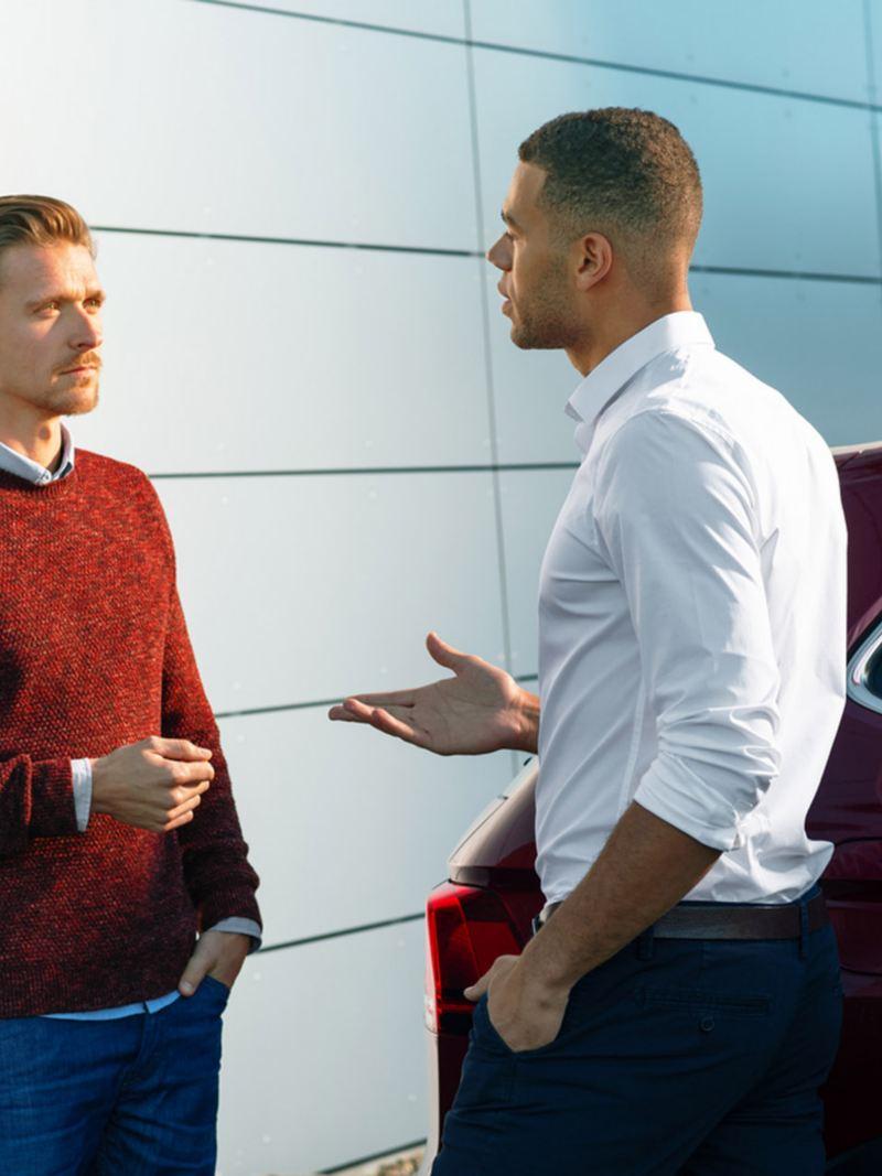 Due uomini discutono a fianco di una Volkswagen