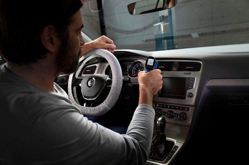 Volkswagen vue de l'intérieur avec un technicien en train de tester la climatisation