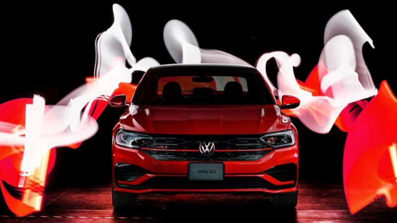 Hombre parado junto al auto deportivo Jetta GLI de Volkswagen en color rojo tornado