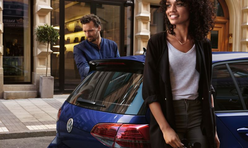 Man and Woman standing next to a Golf, ink out to Vw's owner's manual.