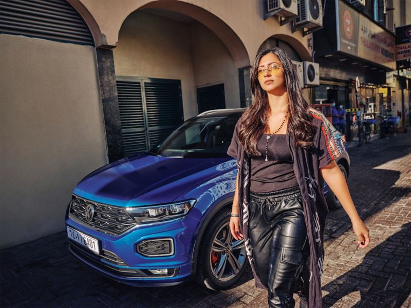 New blue T-Roc parked in town. A woman walking in front of the car