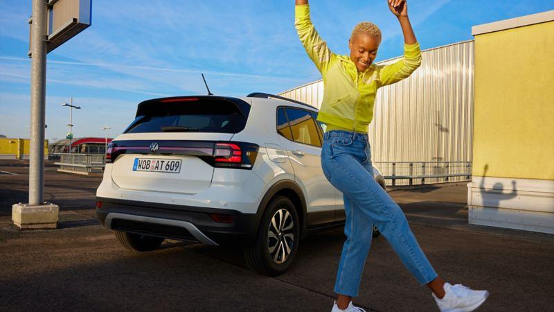 Eine Frau tanzt vor einem weißen VW T-Cross ACTIVE