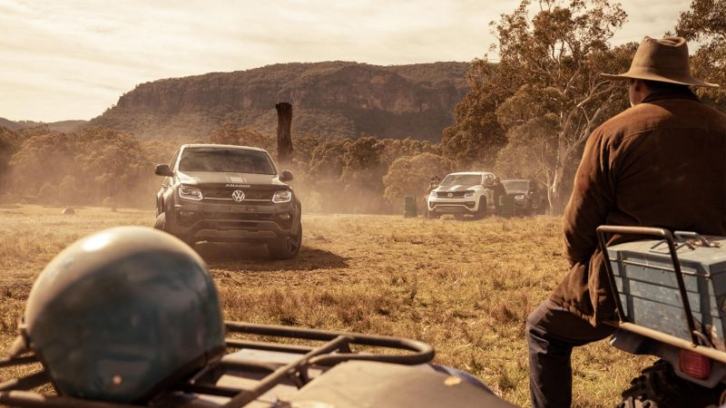 Volkswagen Amarok W-Series driving on paddock with farmer sitting on quadbike in foreground