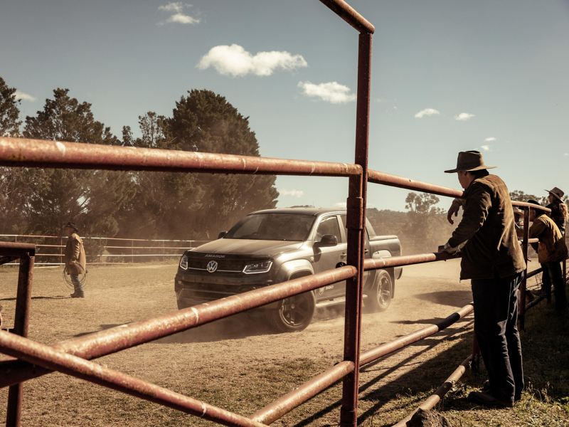 Volkswagen Amarok W-Series drifting in paddock with farmers watching behind fence