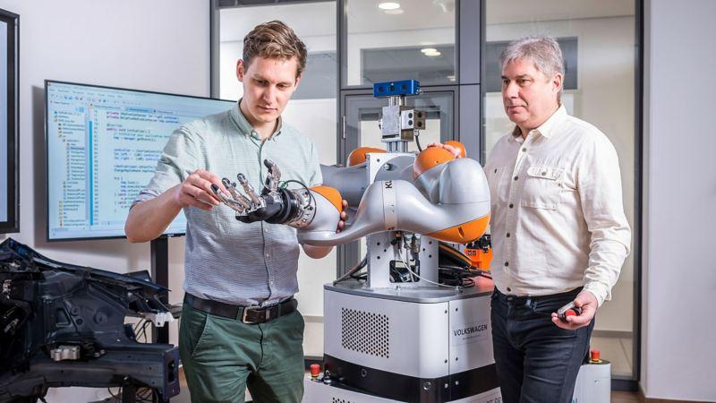 Zwei Mitarbeiter arbeiten an einer Robotorhand