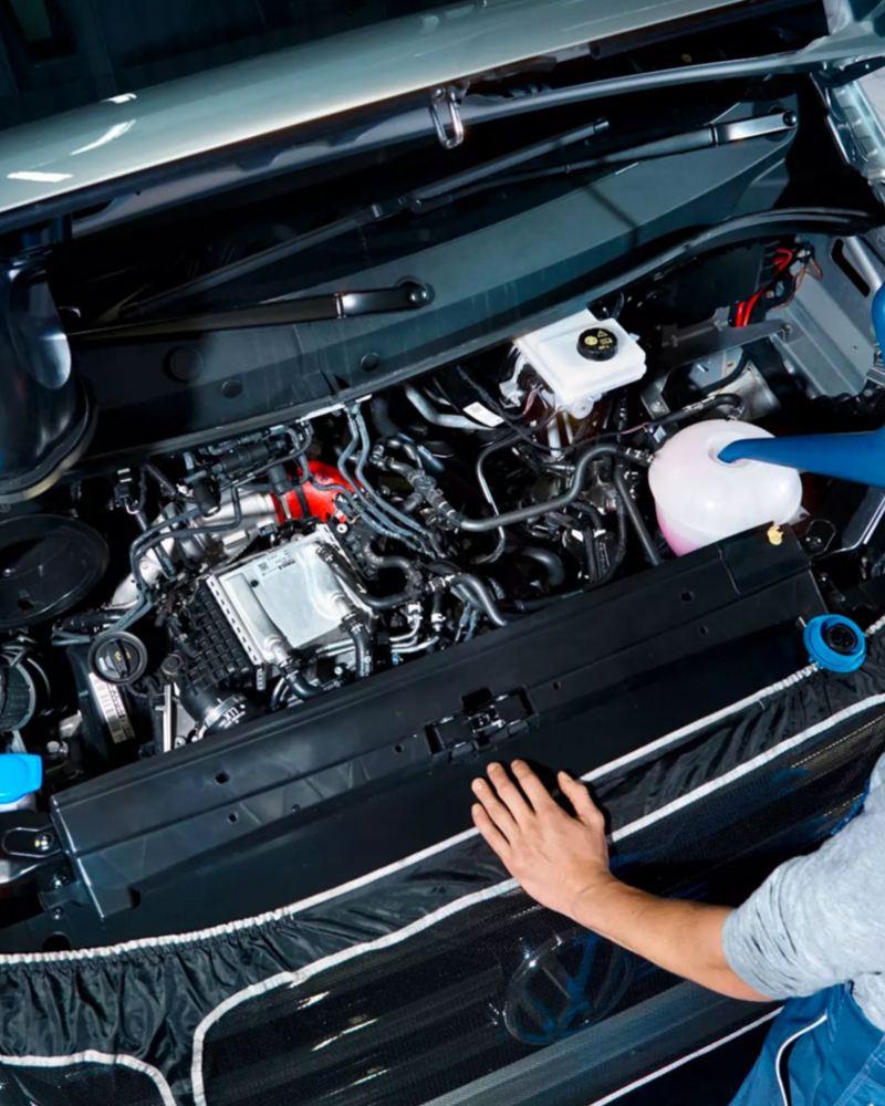 Un meccanico Volkswagen, in piedi davanti al cofano aperto di un veicolo, ne rabbocca i liquidi.